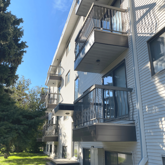 exterior of apartment building with tree and balcony